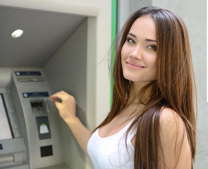 Pani wkładająca kartę do bankomatu